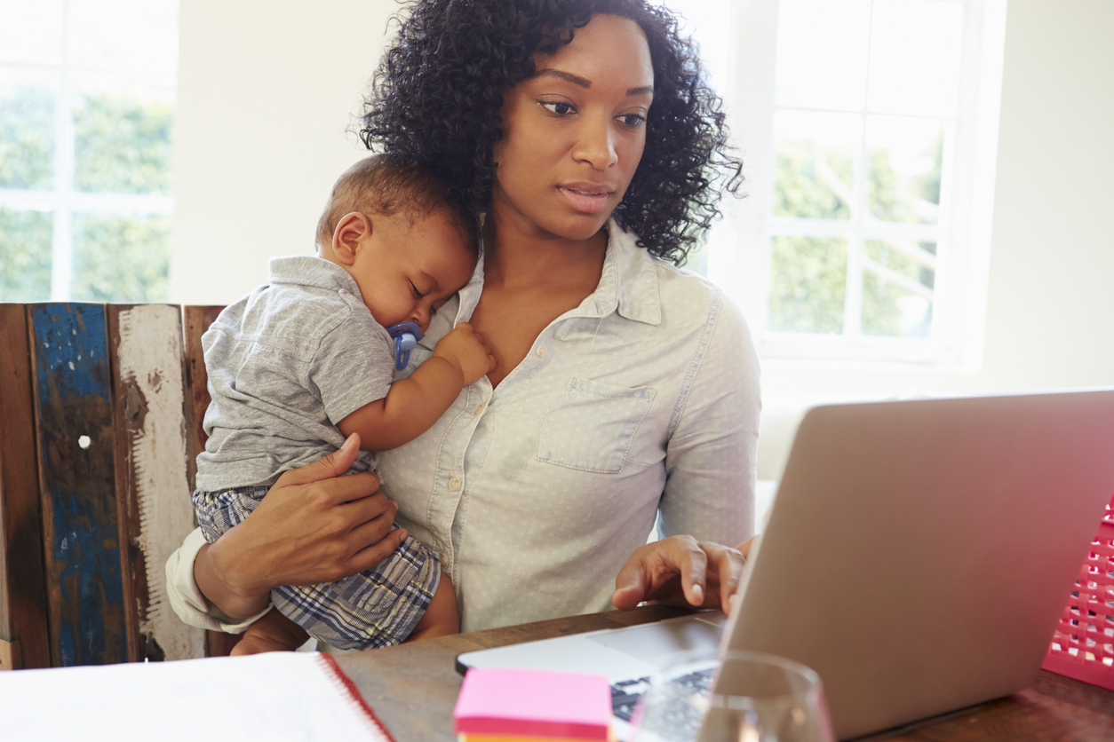a mother holds her baby while working on a laptop